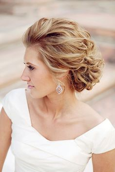 """""""For a more relaxed look, consider the disheveled chignon,"""" says Redmond, which adds subtle, sexy allure to the typically more formal, streamlined chignon. This style works wonderfully for beach or lakeside nuptials, as a gentle breeze only enhances the bounce and volume.Related: 50 Ideas for a Classic Fairy Tale Wedding"""