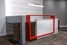 Custom designed reception desk with a welded metal accent painted in bright red to match with L3's branding