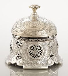 AMERICAN SILVER DINNER BELL Tiffany & Co., New York, New York, circa 1888 Marks: TIFFANY & CO., 9993 M 7353, STERLING-SILVER; The dinner bell encased in cast and chased case of arabesque decoration with pierced grill work crowned with cast push button.