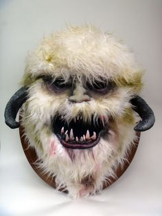 Mounted Wampa Head  Frame is made with cardboard, chicken wire, and foam. The eyes, nose and mouth were made with paper clay. The horns are plaster and he is mounted on an oak plaque. The rest is just fake fur.   Created by Anya Boz