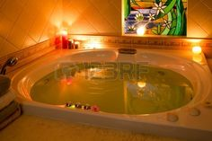 Nice atmosphere in bathroom with jacuzzi filled with water and bath salts, in the candle light. Stock Photo