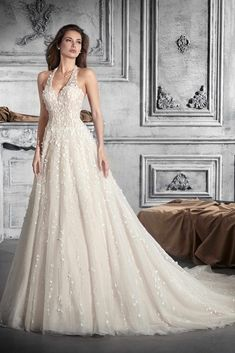 Demetrios Wedding Dress Style 801 Be the belle of your wedding ball in this halter gown. This a-line, tulle number is emphasized by the delicate, flowing flowers and beading.