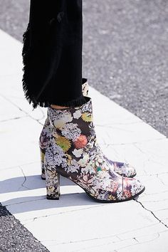 raw-hem black jeans and statement floral print boots
