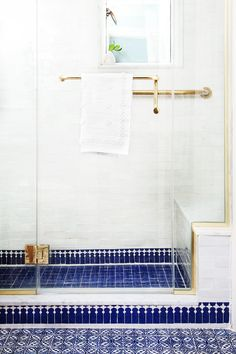 White and Blue Bathroom with handmade Moroccan Tile and Brass fixtures. Mosaic House tiles used: Walls: Bejmat 2x6 tile, Shower Floor: R'Ceef 2x2, Border tile: Zanar, Floor: Handpainted Pigalle 4x4 tile Designer: Indigo & Ochre
