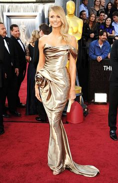 Stacy Keibler is wearing a beautiful gold lame off the shoulder Marchesa gown at the 2012 Oscars