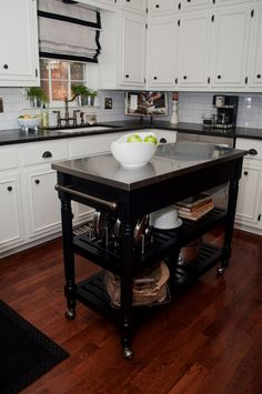 Smaller white kitchen with dark portable kitchen island on wheels. Good use of high cabinets. #Kitchens