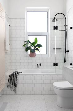 Beautiful bright bathroom with white tile, indoor plant and small bare window.