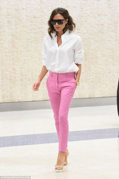 //Slim and trim: Victoria Beckham arrived at John F Kennedy airport in New York City on Monday dressed in a pair of bright pink trousers and a smart shirt