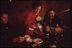 """""""After a cold morning of patrol duty, police officer Shearer and Chief Allec enjoy hot coffee at Mac's Cafe,"""" Rifle, Colorado. David Hiser, January 1973."""