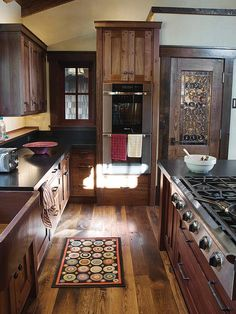 Lovely dark A&C kitchen; love the door with rondels.