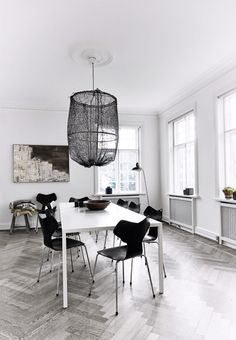 Nordic and modern dining room. The black Grand Prix Dining Chairs by Arne Jacobsen is a beautiful contrast to the white dining table from 1000Chairs.