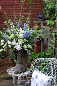 blue delphinium, pussy willows, white roses, white lillies, other white flowers and white wire chair with blue and white pillow