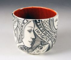 Black and white painted porcelain cup with faces, a frog, a bird and the word Imagine