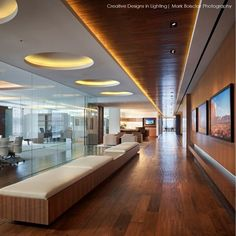 This Real Estate Investment Office designed by Gensler uses clean lines and textured materials to create a modern interior.  Lighting by Walter Spitz was used to highlight architectural detailing and create a golden glow.  Mark Boisclair Photography