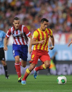 Alexis Sanchez (R) of Barcelona escapes from   Mario Suarez of Atletico de Madrid during the Spanish Super Cup first leg match between Atletico de Madrid and Barcelona at Vicente Calderon Stadium on August 21, 2013 in Madrid, Spain.