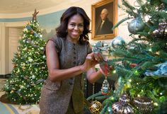 First Lady Michelle Obama holds the 2015 White House Historical Association Christmas ornament as she hangs it on a tree in the Diplomatic Reception Room of the White House on Dec. 10, 2015.