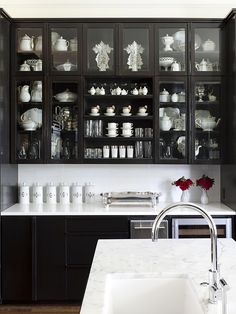 at home arkansas kitchen black cabinets glass doors marble counters via cococozy