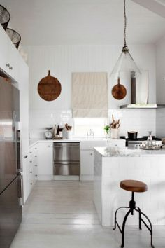 Vintage European timber chopping boards and mango wood stools from Orson & Blake add warmth to the all-white space, which is lit by a recycled glass pendant light. #Kitchen #Country