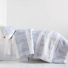 Light blue and white stripes create the laid back look of the Tide Stripe Comforter and Sham Set. The unique and subtle ruching texture sweeps across the face of this comforter, while the back reverse