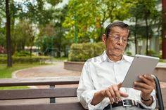 Un anciano disfrutando de sol de la mañana leyendo el periódico desde un iPad Foto de archivo - 17080084