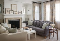 Muted colors make for a relaxing living room. Great windows beside the fireplace.
