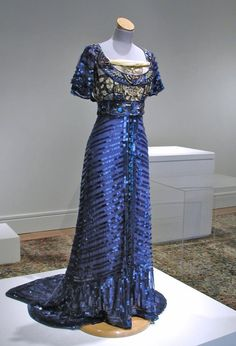 1909 Callot Soeurs royal blue evening gown with empire waist, short sleeves and fishtail hem, skirt has square sequins on net over satin, fitted to fishtail, center front band of large gems, filet lace on bodice.