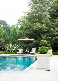 This serene outdoor area, which includes a swimming pool and adjacent brick pavilion, creates a private space to unwind.