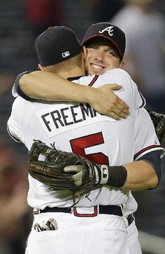Atlanta Braves' Chris Johnson embraces with Freddie Freeman after defeating the New York Mets 5-3 in a baseball game.