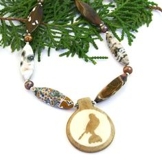 "The one of a kind ""Haru"" artisan necklace was created with a bone falcon bird pendant, earthy ocean jasper in a wide variety of colors, coppery freshwater pearls and sterling silver."
