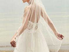 un joli voile à longueur du bout des doigts et une coiffure élégante de mariage en chignon bas
