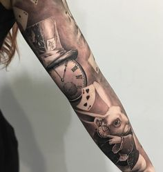 A somewhat Alice in wonderland inspired sleeve tattoo. You can see the mad hatter's hat, the pocket watch, the cards and the rabbit in the design and this helps bring back memories of childhood and the wonderful adventures of Alice.