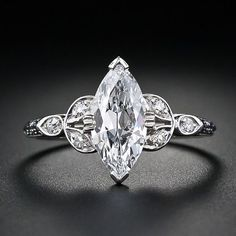 A super high-quality 1.18 carat antique marquise-cut diamond is the star of this stunning vintage platinum diamond engagement ring. The diamond is accompanied by a GIA report stating D color VS2 clarity. Three small accent diamonds are set on either side and further enhanced with a decorative design down each shoulder. Platinum. Art Deco. Interesting use of the marquise