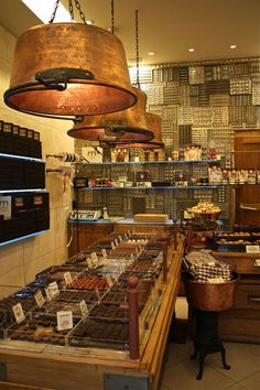 Chapon Chocolaterie | Paris-Genius using old chocolate molds as wall covering and jam pots as lighting. That lighting would be perfect in a kitchen. Love it!