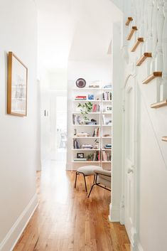 """An existing hallway runs from the entry through a """"reading room"""" to the kitchen. The curved door under the stairs was kept. #dwell #homerenovation #chicago #victorian #beforeandafter"""