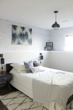 A mix of modern style and industrial decor turned this dreary basement into a dreamy bedroom. The White Heron SW 7627 walls immediately brighten the space while the faux brick DIY wall mural makes the space seem like it was a brick basement to begin with.