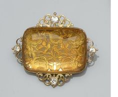 A citrine and diamond panel brooch The shaped rectangular mixed-cut citrine collet set above a pierced and engraved panel, decorated with flowerheads and foliage, in closed-back setting, framed by an openwork scrolling border highlighted with four old-cut diamonds