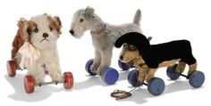 STEIFF DOGS ON WOODEN WHEELS, a Molly, (1317ex), brown and white mohair, brown and black glass eyes, brown stitching, FF button and red eccentric wheels, 1930s --8in. (20.5cm.) long; an Irish Blue Terrier, (1317ex), grey mohair, brown and black glass eyes, black stitching, red colar, blue eccentric wheels and FF button with yellow cloth tag, circa 1940 --8¼in. (21cm.) long (some wear); and a Dachshund, (1317ex), black and light brown mohair, brown and black glass eyes, black stitching…