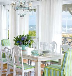 White and Relaxed Mis-matched thrift store chairs are unified with a fresh coat of paint and candy-striped blue and green fabric. A chandelier                          adds glamour to the thrifty dining room.