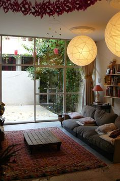 Here we go again. I love the indoor/outdoors feel and the big ball light fixtures. Low lying couch too.