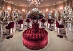 Loja luxuosa de maquiagem Charlotte Tilbury, em Londres. Visual Merchandising e Retail Design. Espelhos com luz, estilo camarim, pufe capitonê bordô, iluminação direcionada.
