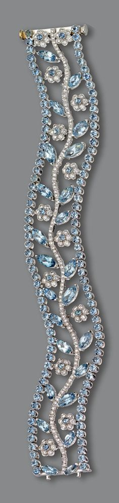 AQUAMARINE AND DIAMOND BRACELET. The openwork serpentine band decorated with a central branch supporting flowers and leaves, set with marquise-shaped and round aquamarines as well as numerous small round diamonds, mounted in platinum, length 7¼ inches.