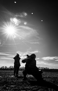 Master Corporal Pat Blanchard from Canadian Forces Combat Camera takes a picture of a U.S. Combat Camera member in action in the drop zone at Plantation Air Park, Sylvania in Savannah during operation SKYFALL in Georgia on March 20, 2015.A black and white image shows the silhouettes of two uniformed Canadian Army Imagery Technicians aiming their cameras up at parachutists falling from the sky.