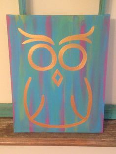 Gold owl with a multicolored background. Background is blue with hints of pink and yellow. Hand painted with acrylic on an 11X14 sized canvas.