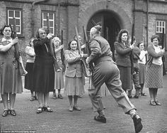A sergeant drilling civilian members of the Women's Home Defence Corps, in the use of rifles during the Battle of Britain in 1940.