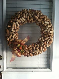 """A cork wreath! I used a plain straw wreath from the craft store, and used approximately 200 or so corks a bartender friend had saved for me. Using a hot glue gun (must be hot, not """"cool"""" or they wont stick) I made about 3 or 4 rows of the corks on the front all lined up tip to tip. Once the rows are set, have fun.. Start gluing the rest of the corks in all different directions. Add a bow and some decorations for any season!"""