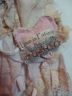 This little vintage cotton baby dress, a pale pink, has been adorned using layers of vintage fabrics and laces.    I created a little heart from