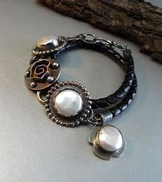 Three beautiful snow white peals adorn this modern bracelet. The pearls measure 14mm around and are set in a 24mm sterling silver setting. The center