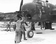 """B-25G Mitchell bomber """"Pride of the Yankees"""" of the 820th Bombardment Squadron. The Armorer is cleaning the bore of its 75mm cannon.  Tarawa, Gilbert Islands - Mar-Apr 1944"""