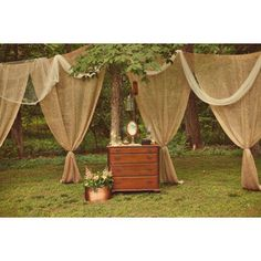 burlap curtains. This is what I'm planning on doing to hide our bathrooms. Burlap curtains hanging on a clothesline from tree to tree with white tulle draped over the top like this. :) Good thing is we can reuse the curtains too!