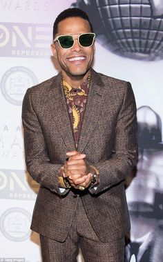 Singer Maxwell wore a patterned brown suit with brown and yellow shirt and white framed su...